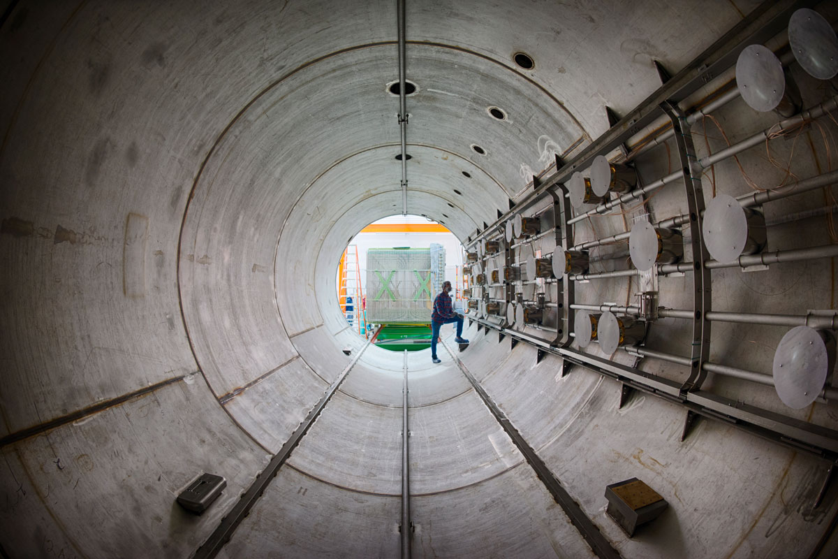 A person stands inside the empty MicroBooNE detector