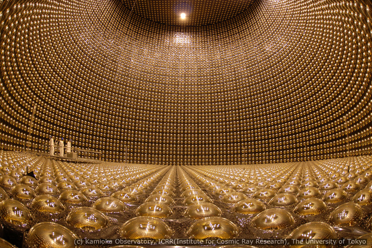 Three people stand inside the Super-Kamiokande detector